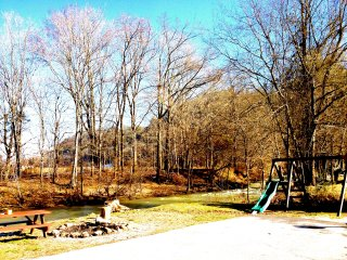 Creek front with 1.3 acres, a game house, hot tub, wifi, fire pit, play set