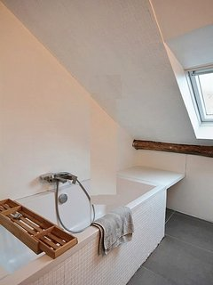 Bathroom 1 is equipped with : washbasin, bathtub with showerhead, toilet, tiled floor. It is between