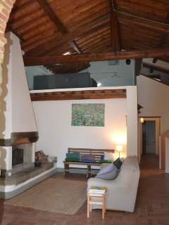 The living room with the fireplace and the mezzanine