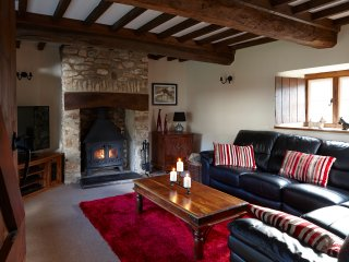 The cosy lounge complete with wooden beams and the stone fireplace housing the log burner.