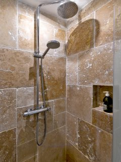 The built-in shower is travertin marble.