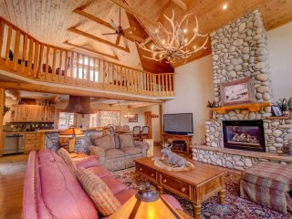 A great room welcomes you with hardwood floors, river stone accents, wood beams.