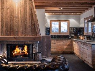 La cuisine ouverte sur la pièce de vie. Le Chesterfield face à la cheminée en bois ancien.