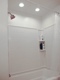 Shower with recessed lighting and shampoo, cream rinse and soft soap provided.