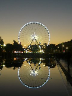 The big wheel reflecting in the water of the fountain area