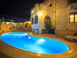 Deck area, swimming pool and outdoor kitchen at night time