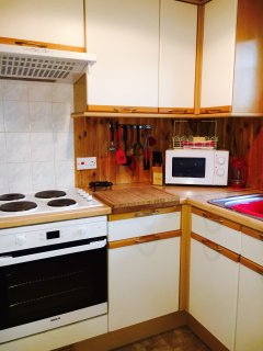 Kitchen with washing machine, fridge/freezer, microwave and lots of storage
