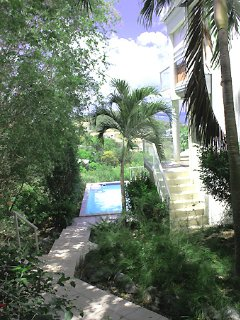 A tiled walkway on the left side of the villa leads down to the Lower Unit and the pool