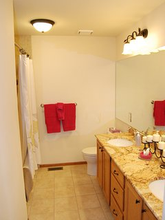 Large hall bathroom has two sinks and a granite counter top