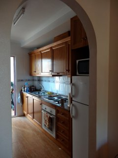 Efficient galley kitchen with electric cooker, fridge freezer and storage units.