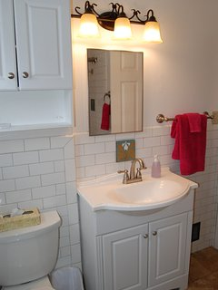 Bathroom has extra supplies in cabinet above toilet