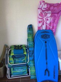 Sedie a sdraio, ombrellone, casse di ghiaccio, boogie boards situati nel ripostiglio Lanai