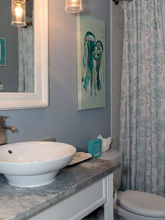 The roomy hall bath has a shower/tub and vessel sink.