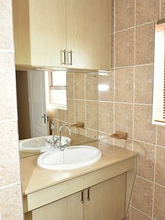 There are built-in cabinets above and below the bathroom sink as well.