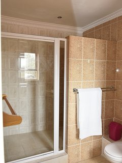 The enclosed bathroom has a double shower and is fitted with a water saving shower head.