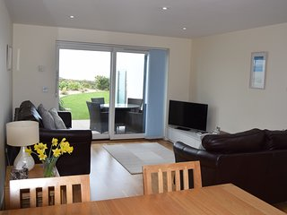 The spacious open plan living room opens out onto a private sea facing patio and communal gardens.