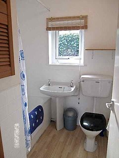 Bathroom with short bath and electric shower over.  Heated towel rail and warm airing cupboard.