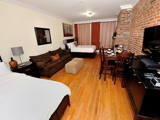 Snuggle up in this huge studio with incredible exposed brick in Midtown West