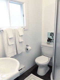 Bathroom has a corner shower stall.
