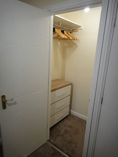 Walk in closet in twin bedroom without en-suite bathroom.