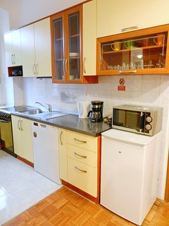 The well-equiped kitchen area with stove, dishwasher, microwave...