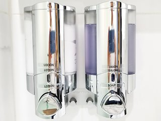 Chrome soap and lotion dispensers accent the bathrooms