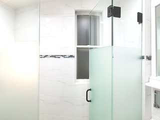 Ultra luxurious custom-tiled frosted glass-enclosed shower with industry's best rain shower head