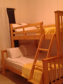 The second bedroom has one twin bed, one full bed, one side table and wall to wall closet.