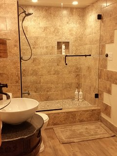 Limestone and tile custom shower in the ensuite adds some rustic luxury to this cozy space.