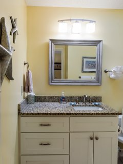 The updated master bath has an over-sized vanity with granite counters.