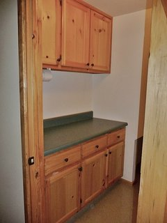 Laundry room cabinets where you can store detergent and a counter for folding clothes.