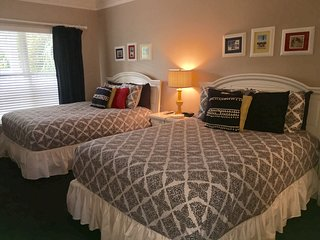 Guest bedroom with two queen beds and remodeled full bathroom.