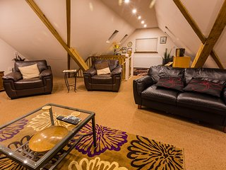 The spacious living area is upstairs with comfortable seating for up to 6 guests.
