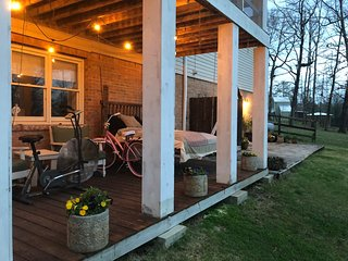 Nice deck outside The Apartment with hanging bed and outdoor seating.