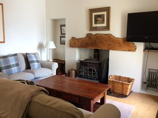 Sitting room with flat screen TV, and wood burning stove.