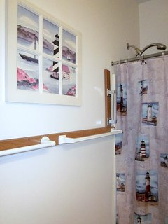 Grab bar beside tub in master bath and plenty of places to hang towels.