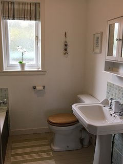 Pretty bathroom with wc, sink, bath with shower over.