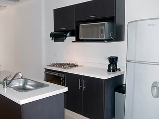 Open kitchen with coffee maker, microwave, oven and fridge. Dishware and glasses set for four.