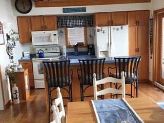 Kitchen area - stove, microwave, dishwasher, refrigerator, coffee maker and breakfast bar.