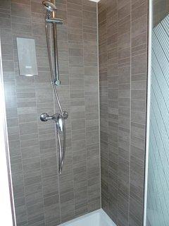Salle d'eau avec douche, lavabo et WC.