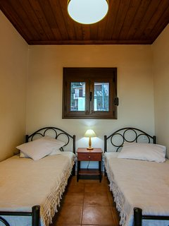 First floor bedroom with two single beds and private balcony overlooking the pool area.