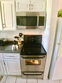 Fully equipped kitchen with fridge, over, microwave, kettle
