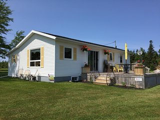 A view from the Southwest side of cottage. Large window is in sunroom. Canada Select sign is on deck