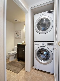 The washer and dryer are located next to the downstairs bathroom