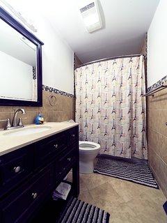 Main bathroom on 1st floor with heater fan, tile bath, nice Kohler shower head, dual flush toilet