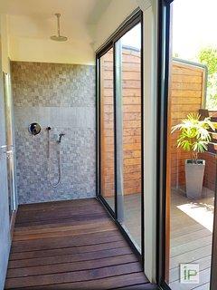 La salle de bain avec douche à l'italienne ouverte sur une terrasse privative