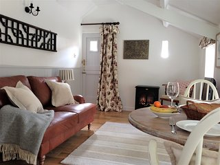 The cosy lounge/dining room with leather sofa, painted table & chairs and lots of light.