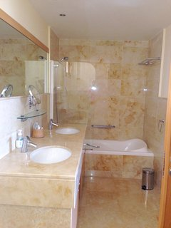 En suite bathroom to master bedroom with bath with shower. 2 wash basins, toilet and bidet.