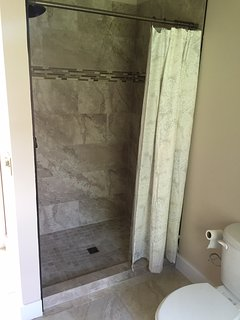 Bathroom with tiled shower stall.