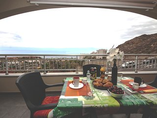 Wonderfull balcony with sofa and table with chairs to eat in front of the sea.
